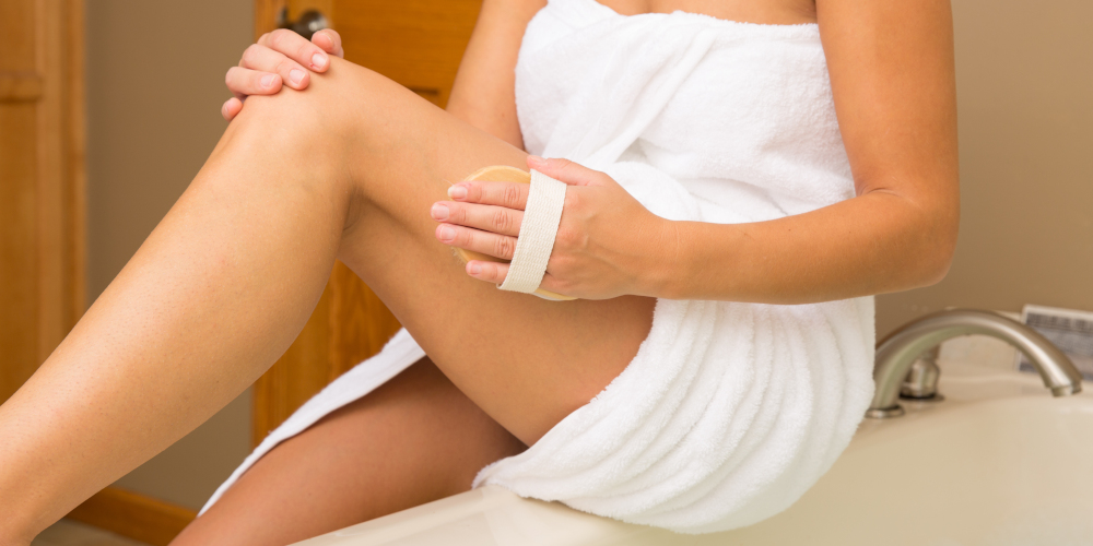 Woman sitting on bathtub performing dry brushing for anti cellulite