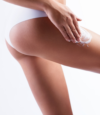 Woman in white underwear applying anti-cellulite-cream on thighs